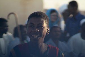 Dansende derwisjen in Sudan - lachende jonge man bij de Halgt Zikr