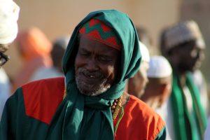 Dansend derwisjen in Sudan - een Sufi gekleed in het rood en groen bij de Halgt Zikr