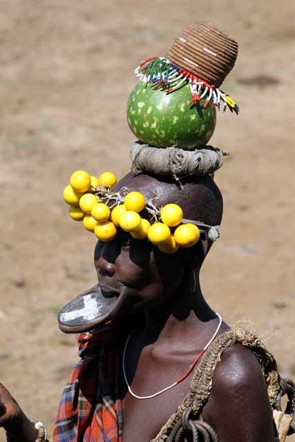 Mursi-vrouw in Ethiopië met lipschotel en rijk gedecoreerd hoofddeksel