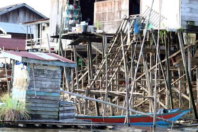 Mahakam rivier in Kalimantan: Mikado van palen voor de paalwoningen langs de Mahakam rivier