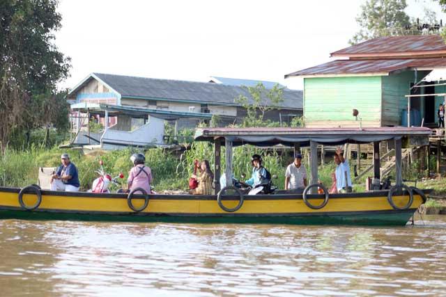Mahakam rivier in Kalimantan: Het pontje voor scooters over de Mahakam rivier