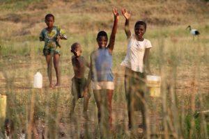 Kinderen zwaaien langs de oever van Queen Elizabeth National Park in Uganda