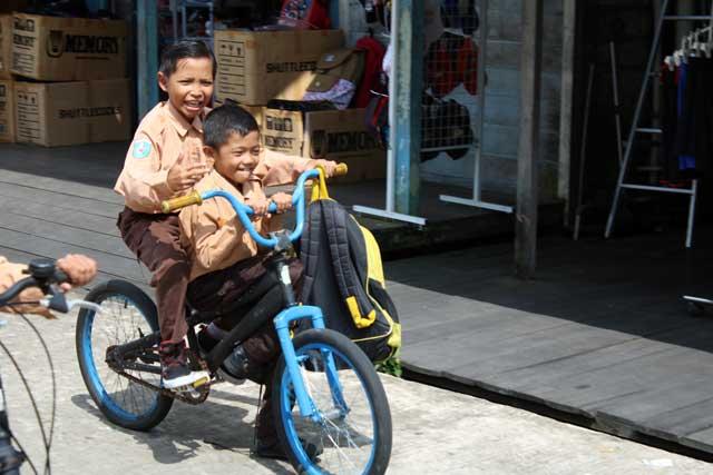Mensen langs Mahakam rivier in Kalimantan - Schooljongens op de fiets