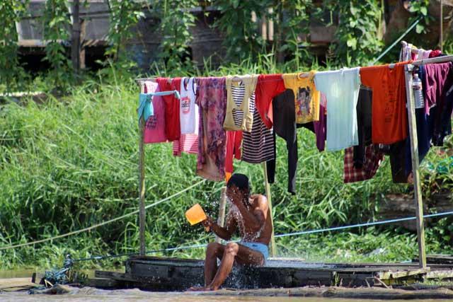 Mensen langs de Mahakam rivier in Kalimantan - Man wast zich onder het drogende wasgoed