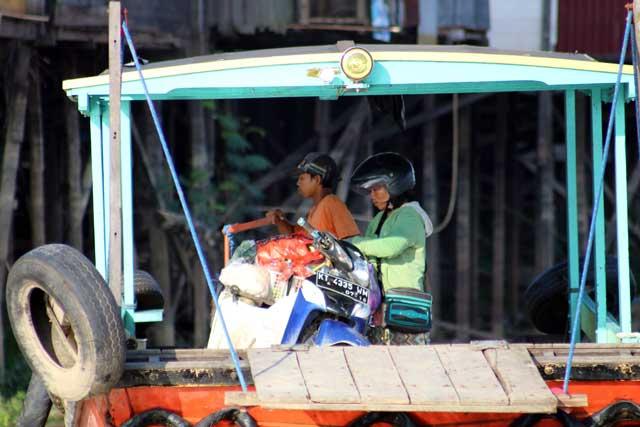 Mensen langs de Mahakam rivier in Kalimantan - Met brommer op pontje de rivier over