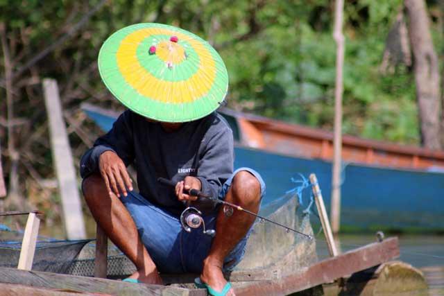 Mensen langs de Mahakam rivier in Kalimantan - Man vist met hengel