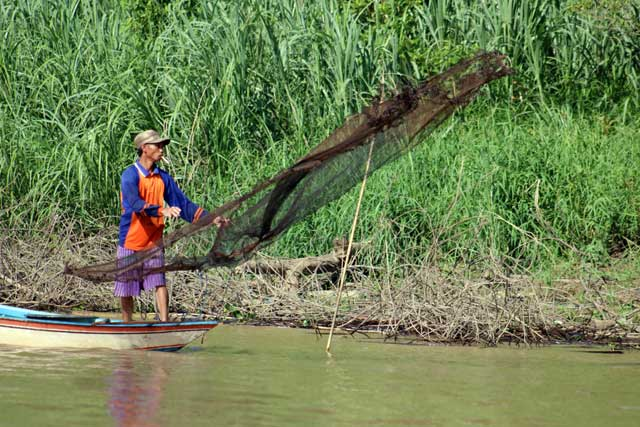 Mensen langs de Mahakam rivier in Kalimantan - Visser gooit zijn net uit