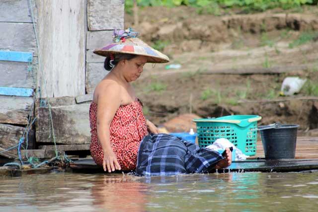 Mensen langs de Mahakam rivier in Kalimantan - Vrouw doet de was