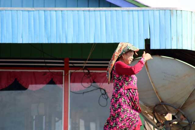 Mensen langs de Mahakam rivier in Kalimantan - Wandelende vrouw
