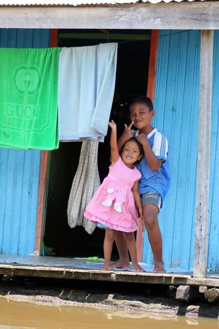 Mensen langs de Mahakam rivier in Kalimantan - Zwaaiende kinderen